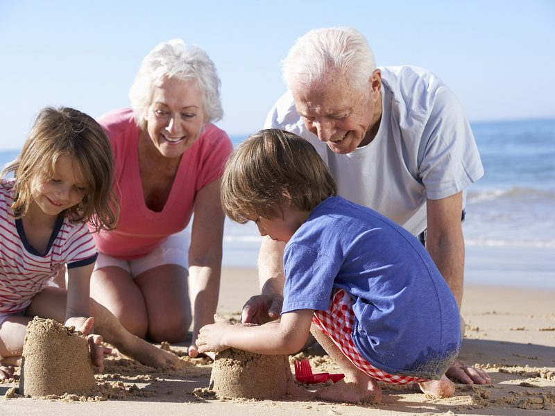 Two grandparents kneel on the beach making sandcastles with two grandchildren